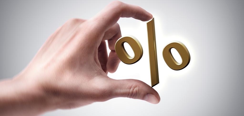 Man's hand holding golden percent symbol